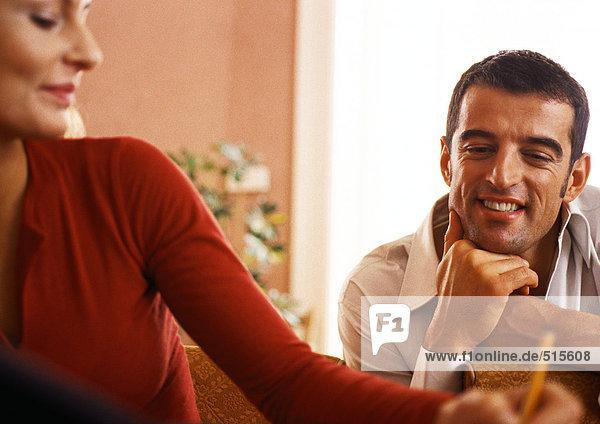 Man smiling  watching woman write