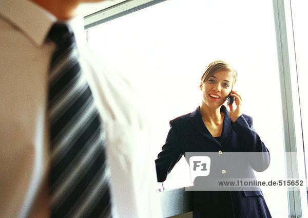 Geschäftsfrau am Telefon  Geschäftsmannbrust im Vordergrund  Nahaufnahme