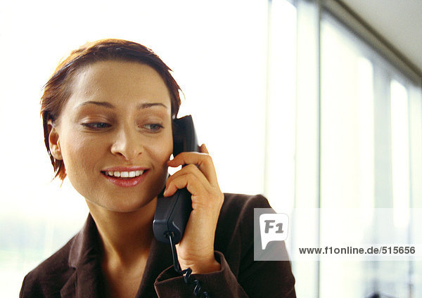 Businesswoman on phone  smiling  head and shoulders  close-up