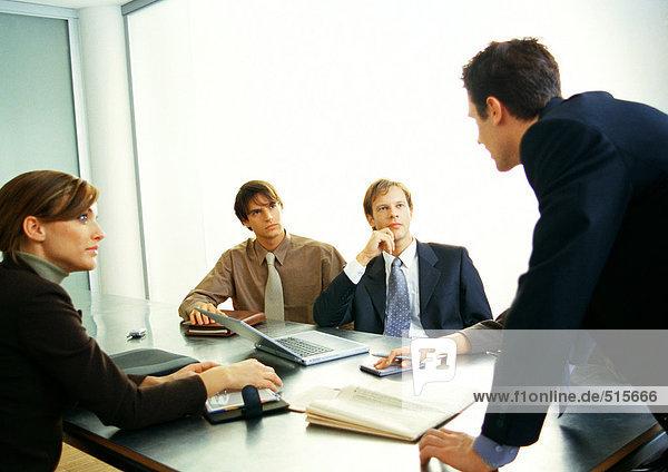 Geschäftsleute  die den Geschäftsmann im Stehen betrachten.