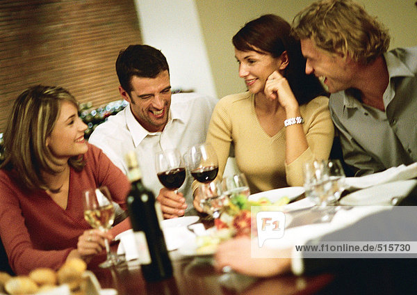 Group of young people around table  drinking wine and laughing