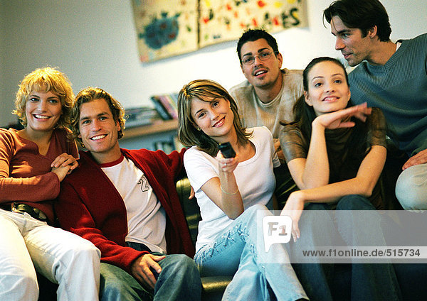 People sitting together on couch  one woman holding remote