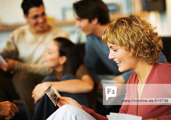 Frau schaut sich das Foto an  Gruppe von Menschen sitzt  redet im Hintergrund