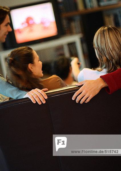 Menschen sitzen auf der Couch  reden  Rückansicht  Fernseher im Hintergrund