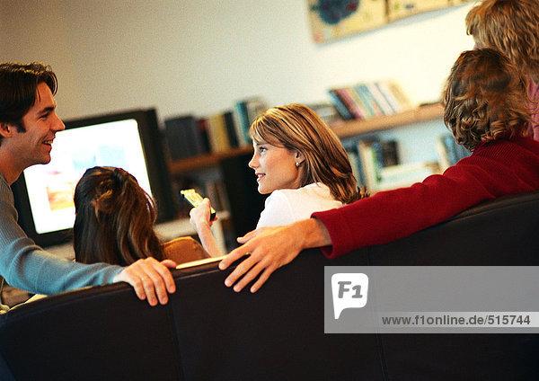 Menschen sitzen auf der Couch  reden und fernsehen  Rückansicht