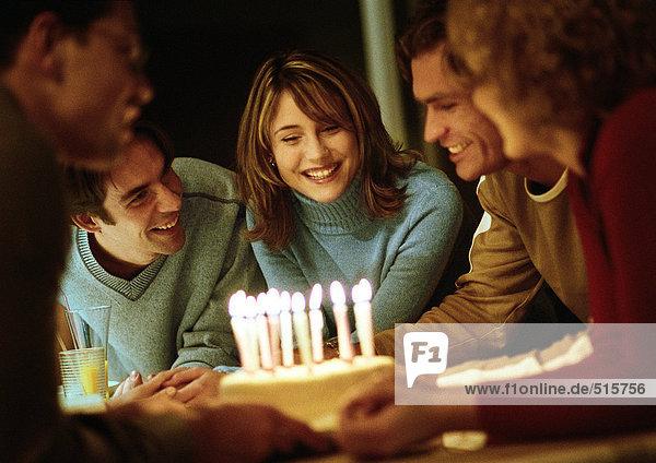 People gathered around birthday cake