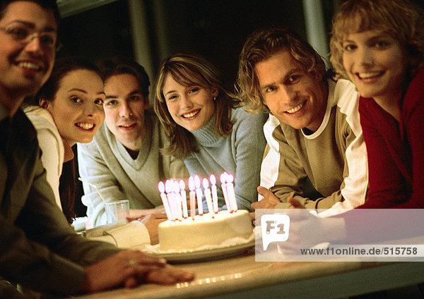 People sitting around birthday cake  portrait