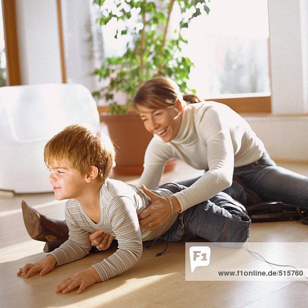 Mutter packt Sohn  auf dem Boden