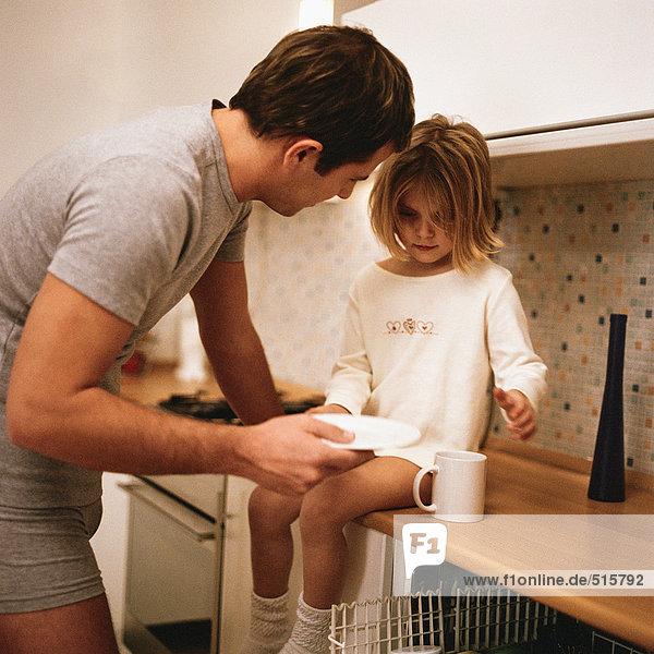 Tochter auf dem Tresen sitzend  Vater stehend zu ihr geneigt