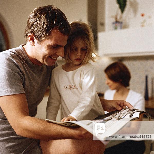 Vater sitzend mit Tochter auf Papier schauend  Frau im Hintergrund