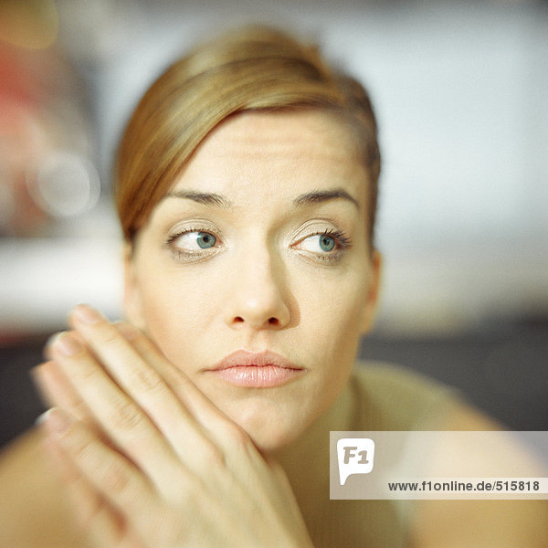 Young woman  hands to chin  looking to the side  portrait