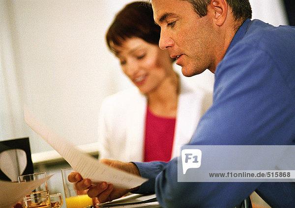 Geschäftsfrau sitzt neben dem Geschäftsmann und liest Dokument  Seitenansicht  Nahaufnahme