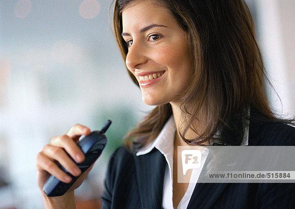 Geschäftsfrau lächelt  hält Handy in der Hand