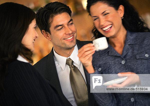Geschäftsmann und Geschäftsfrau beobachten zweite Geschäftsfrau beim Kaffeetrinken  Lachen