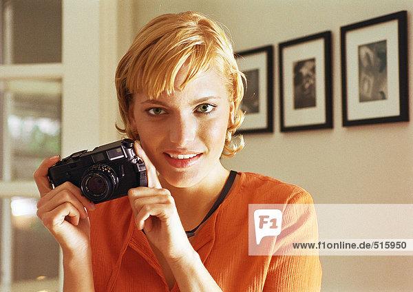 Teenage girl holding camera  smiling