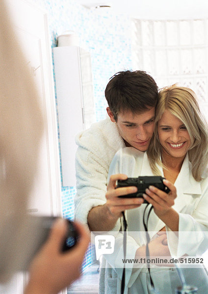 Couple taking photo of themselves in front of mirror