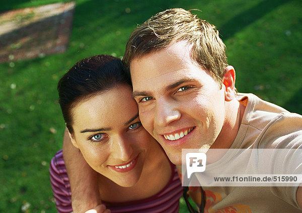 Ein Paar lächelt in die Kamera  der Arm des Mannes um die Schulter der Frau.