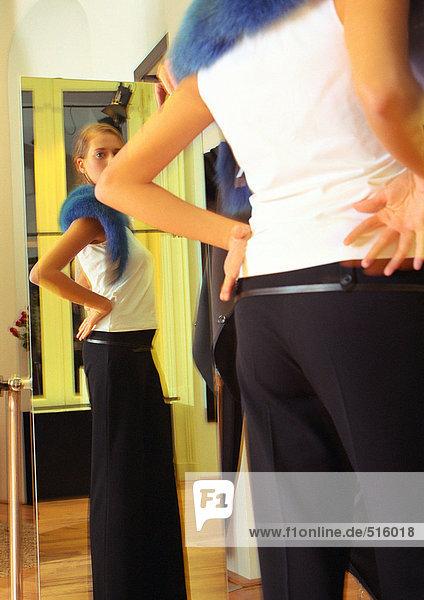 Junge Frau beim Anprobieren  Blick in den Spiegel  Rückansicht  Seitenansicht