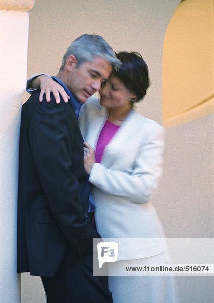 Mann lehnt sich an die Säule  Frau legt den Arm um ihn herum
