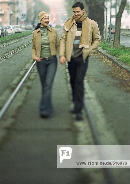 Ein Paar geht die Straße entlang und hält sich an den Händen.
