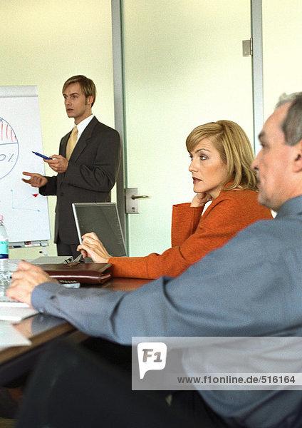 Gruppe von Geschäftsleuten  die am Tisch sitzen und sich treffen.