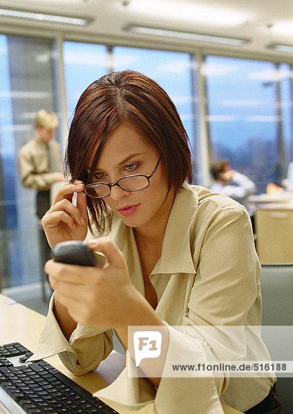 Geschäftsfrau  die eine Brille anpasst und auf das Telefon schaut  im Büro  Nahaufnahme.