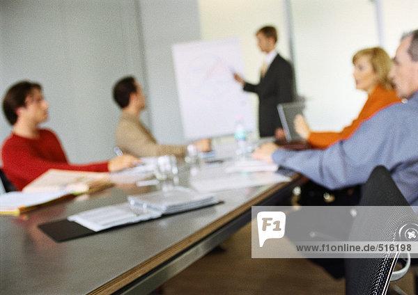 Geschäftsleute sitzen am Tisch in einer Besprechung  verschwommen.