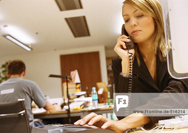 Geschäftsfrau wählt Telefon im Büro.
