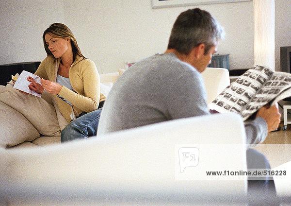 Mann und Frau sitzen auf der Couch und lesen