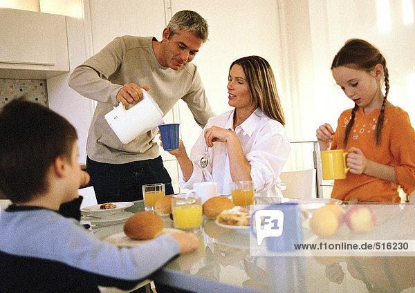 Familie beim gemeinsamen Frühstücken  Vater beim Trinken