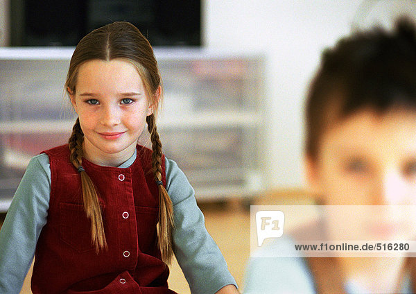 Young girl with pigtails smiling  waist up  and boy  blurred in foreground  portrait