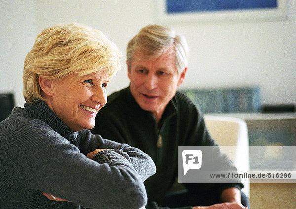Seniorin sitzend mit über die Brust gefalteten Armen  Seitenansicht  Senior Mann im Hintergrund  Blick auf Frau  Kopf und Schultern