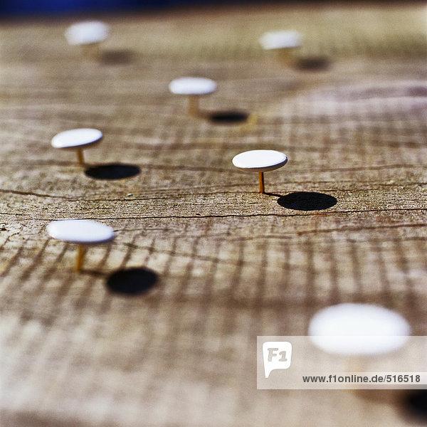 Daumennägel in die Holzoberfläche geklebt