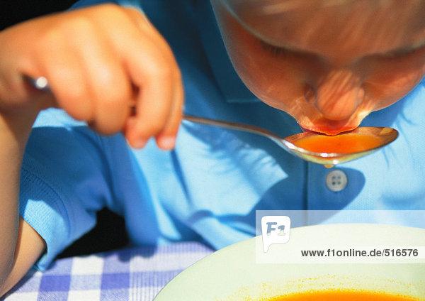 Kinder essen Suppe mit Löffel