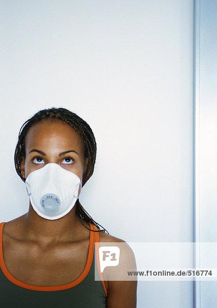 Frau mit weißer Staubmaske über Nase und Mund  Portrait