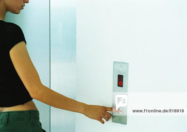 Frau drückt Fahrstuhlknopf