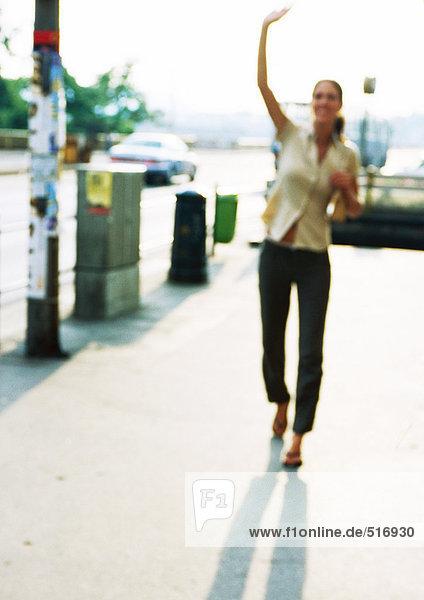 Frau auf dem Bürgersteig  Hand hoch  verschwommen