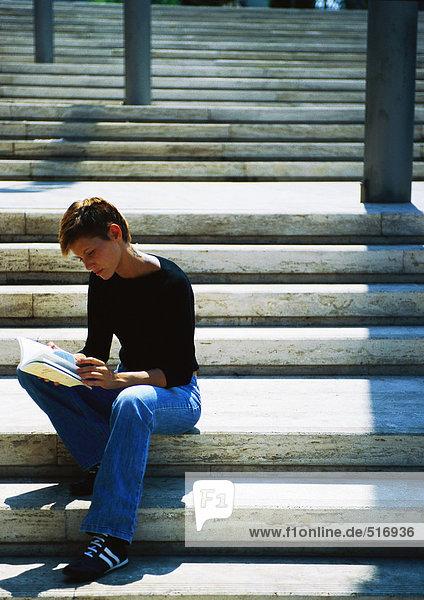 Frau auf der Treppe sitzend  lesend