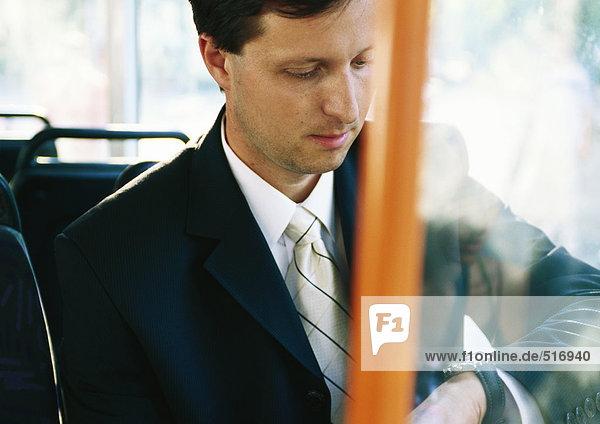 Geschäftsmann sitzt im Bus und kontrolliert die Uhr.