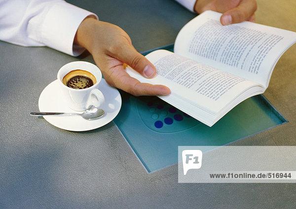 Männerhände halten Buch neben Tasse Espresso