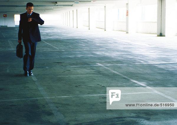 Geschäftsmann  der im Parkhaus spazieren geht und die Zeit überprüft.
