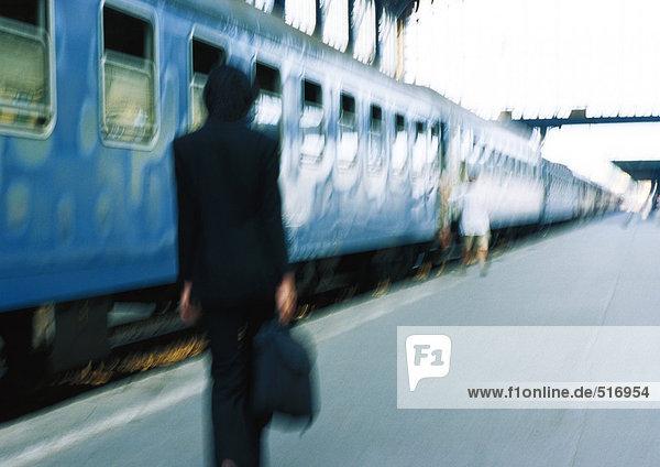 Geschäftsfrau auf dem Bahnsteig neben dem Zug  Rückansicht  verschwommen