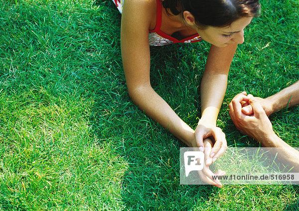 Frau auf dem Bauch auf Gras liegend  Hände zusammen  neben Männerhänden  Nahaufnahme
