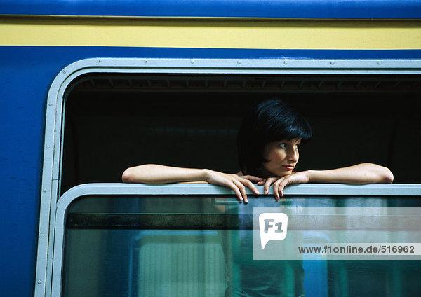 Frau im Zug  aus dem offenen Fenster schauend