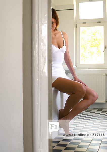 Junge Frau auf Badewannenrand sitzend  durch die Tür gesehen