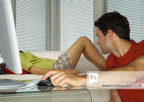 Mann schaut vom Computer weg auf die Frau  die auf dem Sofa liegt.