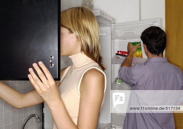 Junges Paar in der Küche  Frau öffnet Schrank  Mann nimmt Gegenstand aus dem Kühlschrank