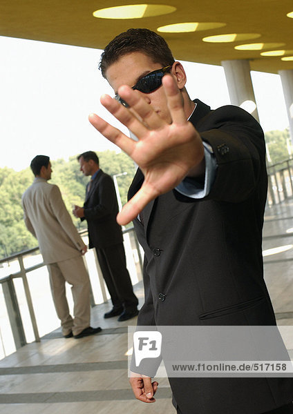 Bodyguard hält die Hand vor der Kamera  während sich zwei Männer im Hintergrund unterhalten.