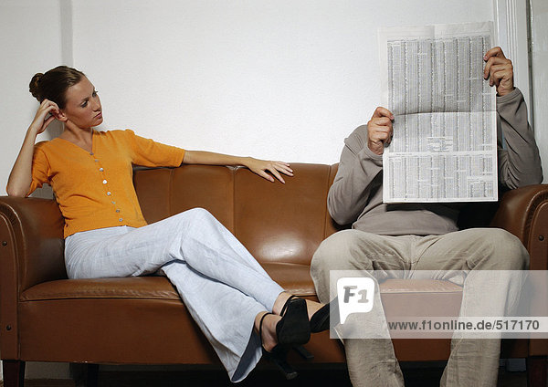 Mann und Frau sitzen auf dem Sofa  Mann liest Zeitung