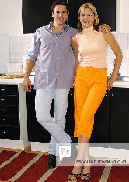 Junger Mann mit Arm um die junge Frau  lächelnd und stehend in der Küche.